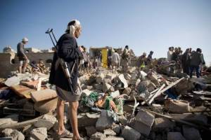 Houthis search the rubble of Sanaa for fallen comrades. Credit: The Independent